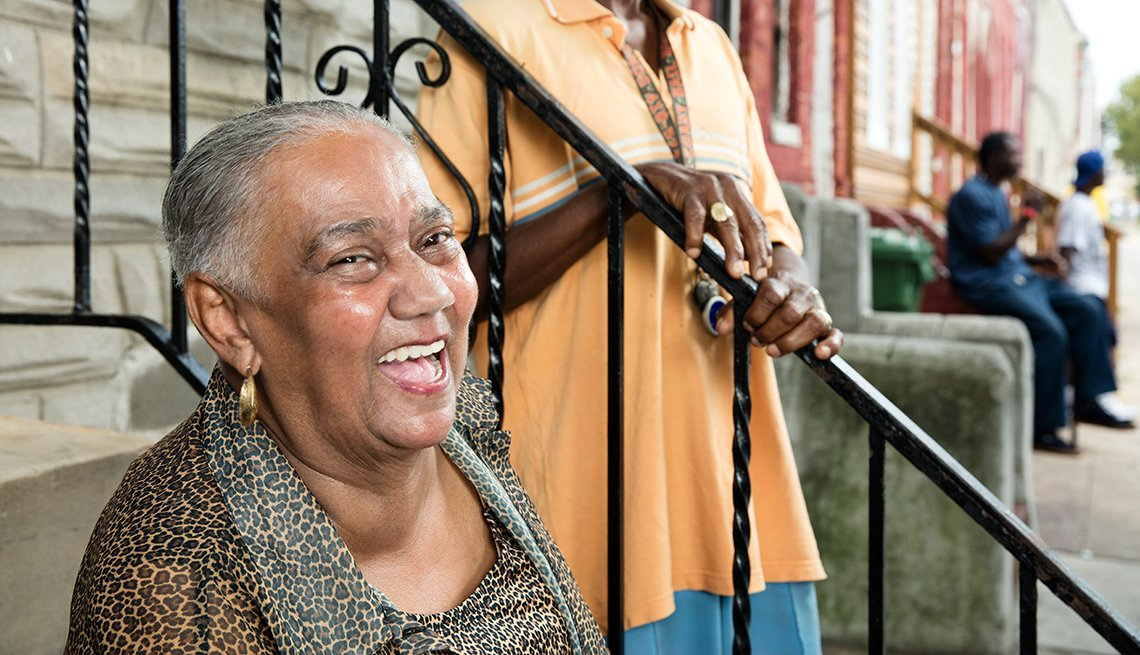Alethea Booze Laughs as she visits with neighbors on the stoop of her row house in Baltimore's Sandtown neighborhood.