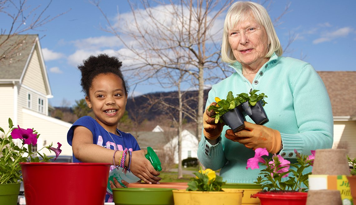 Mary Steele, right, plant flowers with a foster child at Treehouse Community in Massachusetts.