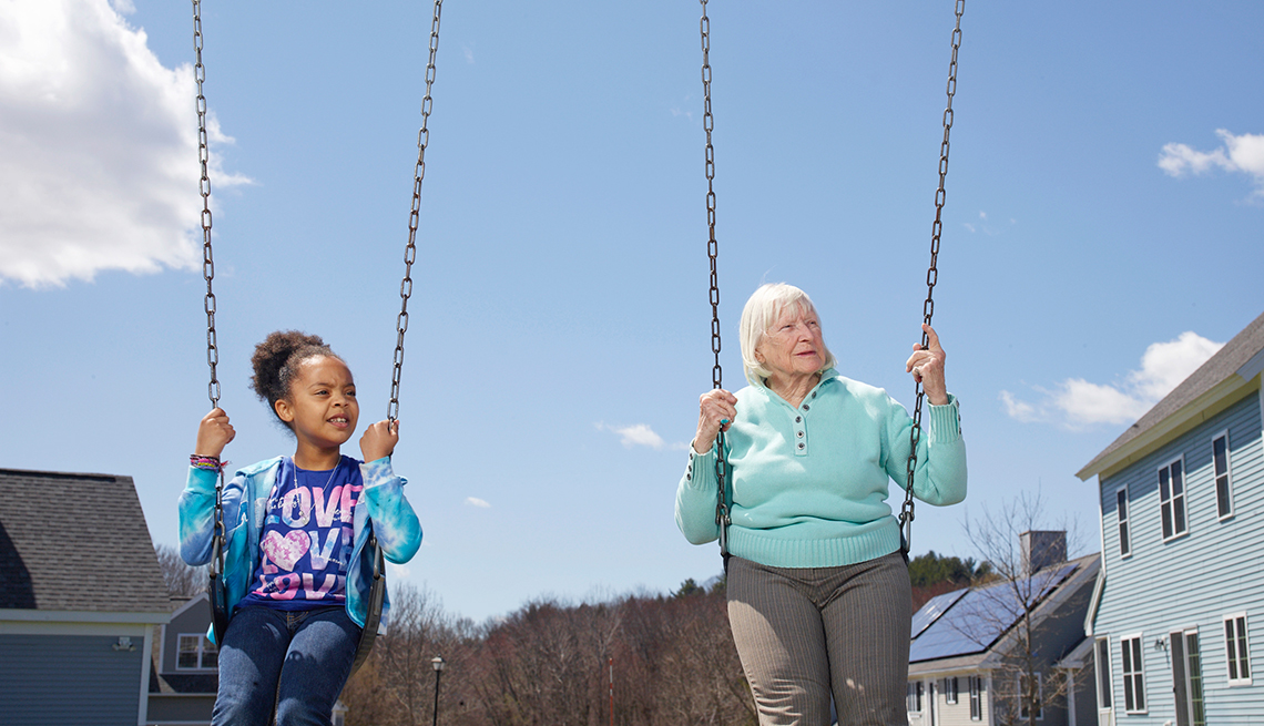 Mary Steele, right,  swings with a foster child at Treehouse Community in Massachusetts.