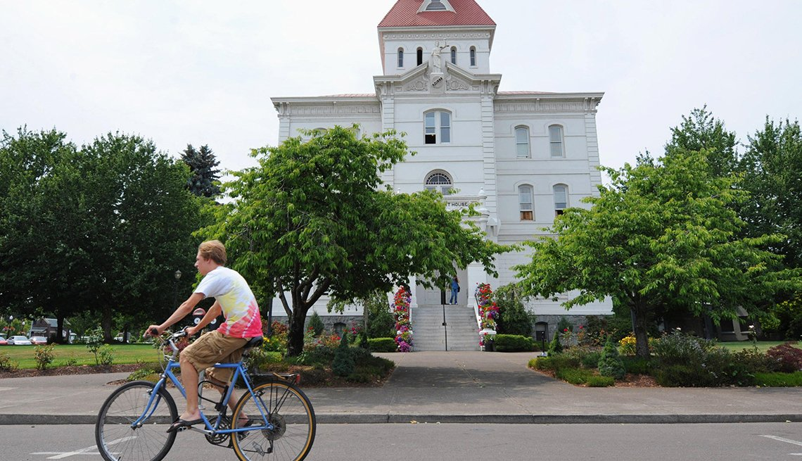 Bicyclist rides by building in downtown Corvallis Oregon.