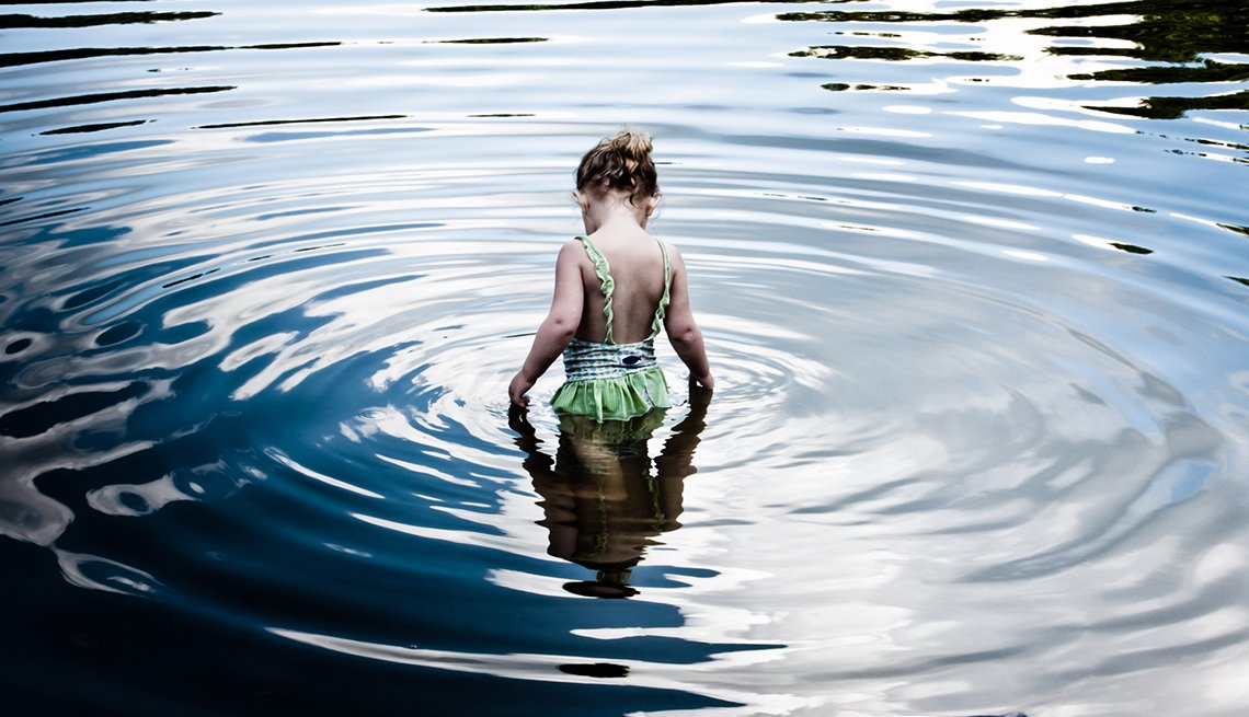 Young girl wading in a river.