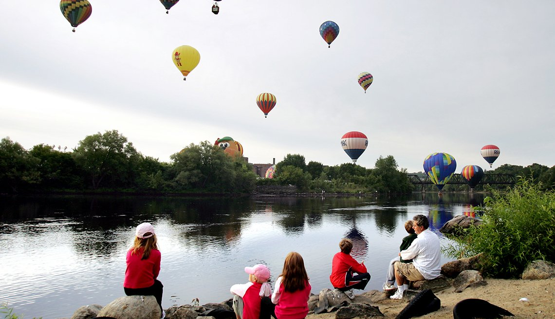 Family watches hot air balloons in the air by a river.