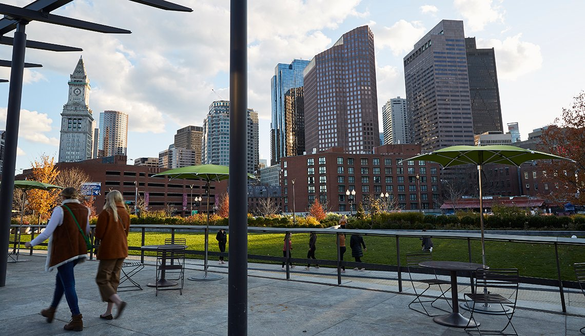 two people walk along the greenway park area in boston with the city skyline rising up above them across a lawn