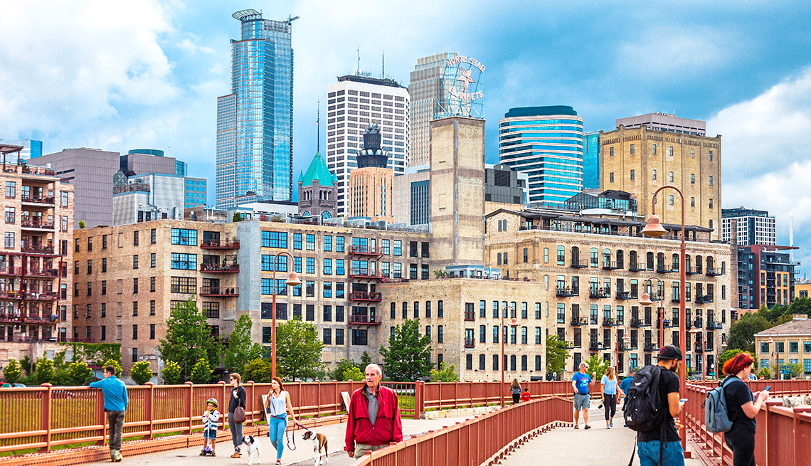 People walking on stone arch bridge across the Mississippi River in Minneapolis with the city skyline above