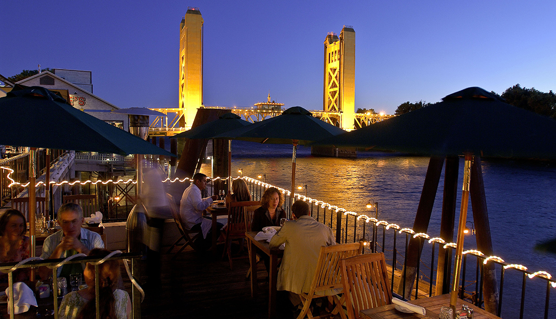 Open air restaurant along the Sacramento River in the evening with a view of the tower bridge in the background