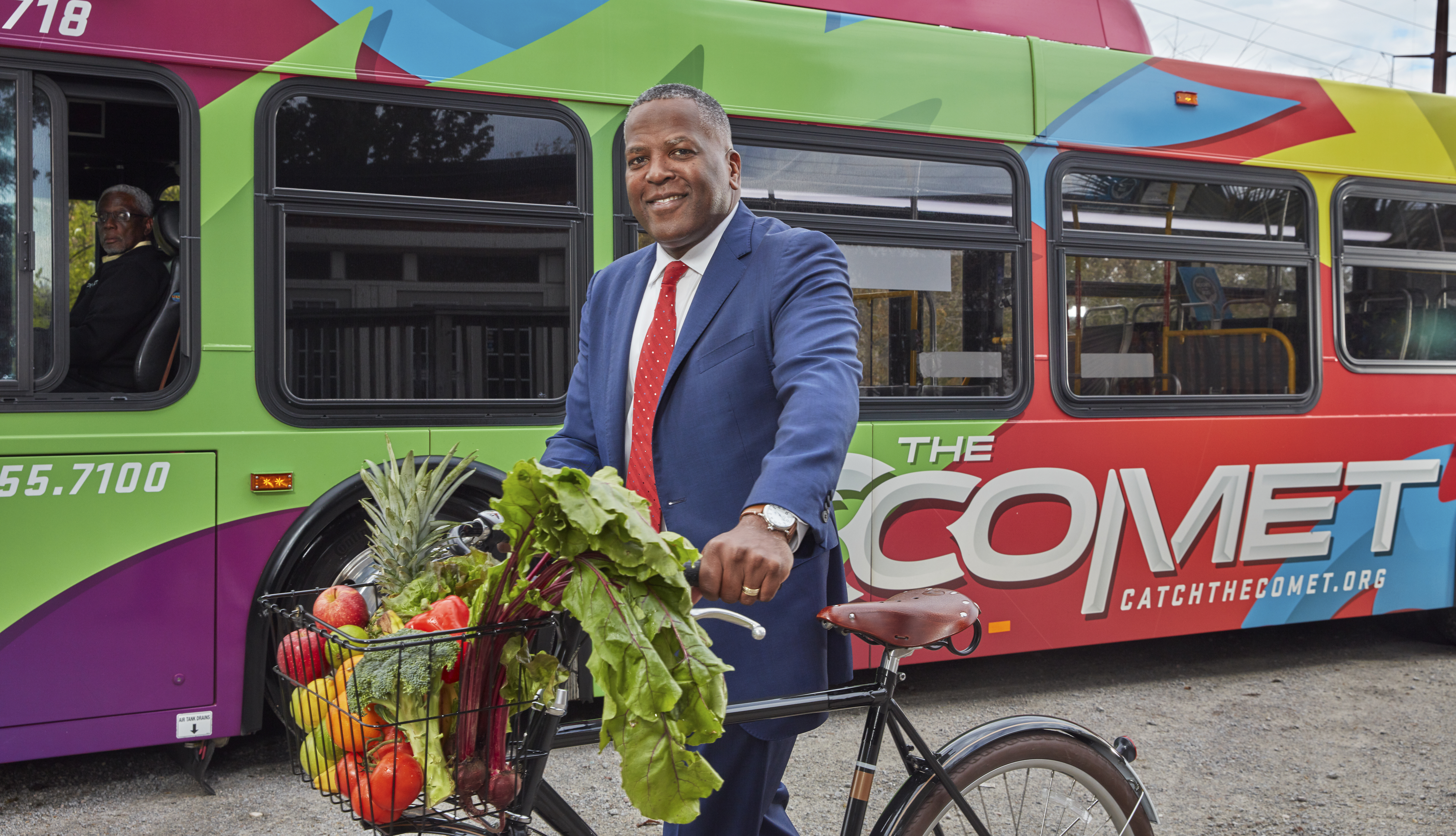 columbia south carolina mayor steve benjamin poses with a bicycle in front of a city bus