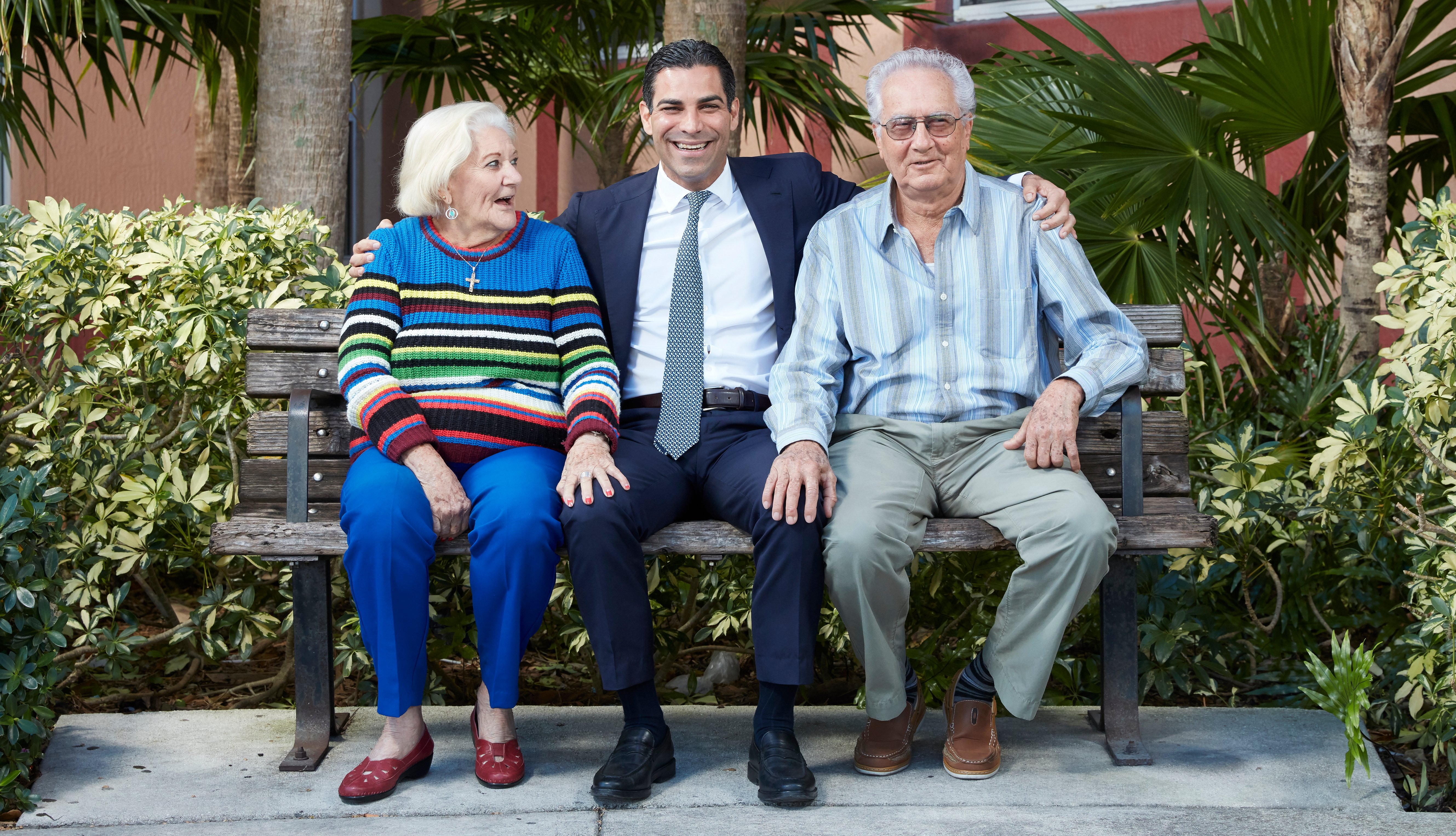 miami florida mayor francis suarez sits on a bench outside an apartment building with two residents