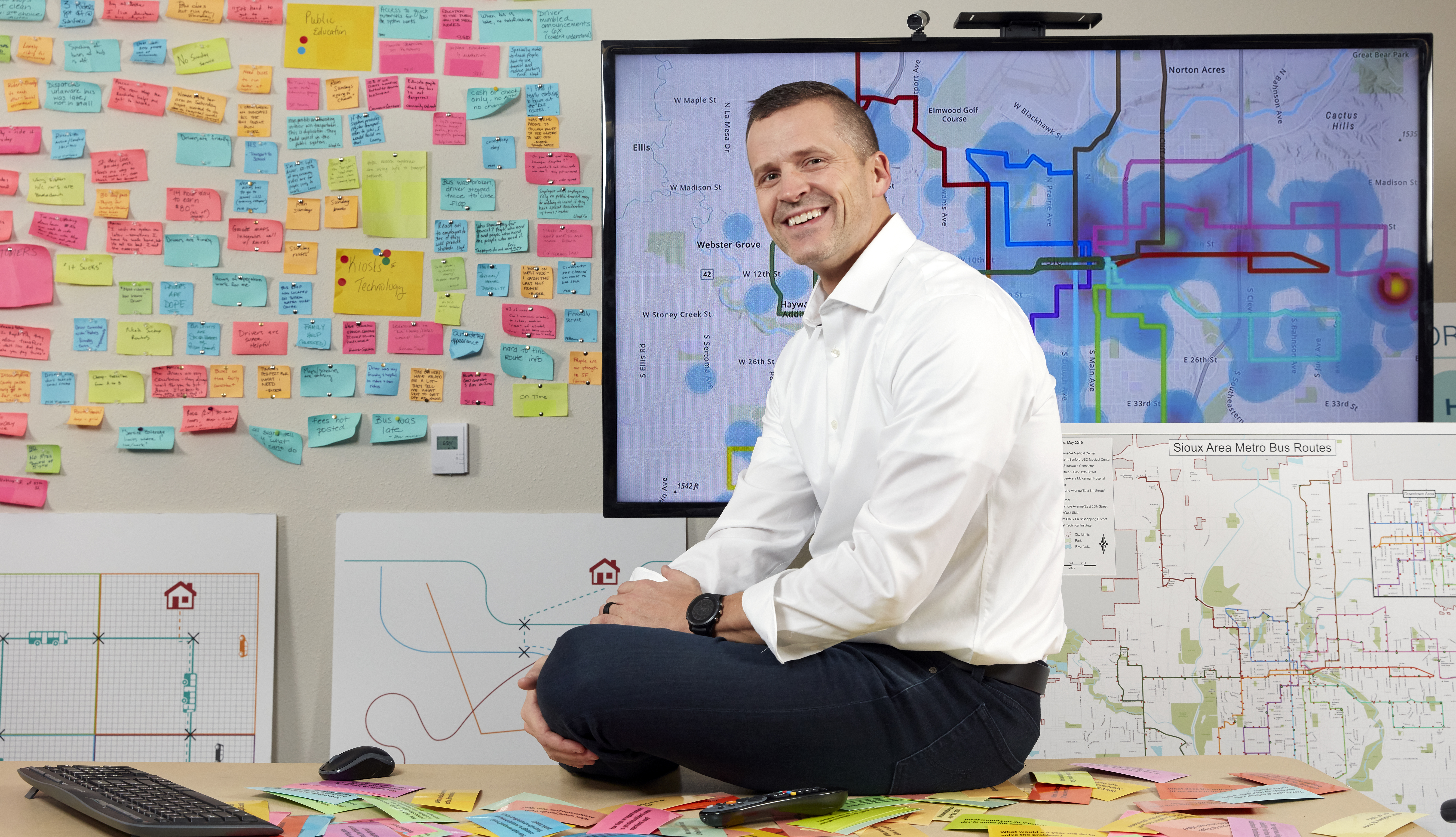 paul tenhaken the mayor of sioux falls south dakota sits on the desk in his planning office where the walls are covered in colorful post it notes and maps