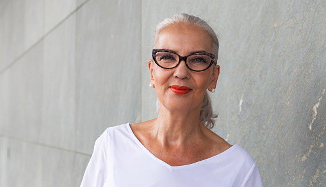 Mujer mayor con lentes, pelo recogido de color gris, sonríe.