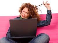 Enriquezca sus conocimientos en línea - Mujer viendo la pantalla de un computador que sostiene en las piernas.