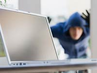 Persona viendo por la ventana un computador - Apps contra robos de móviles, tabletas o gadgets.