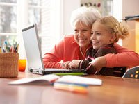 Grandmother embracing her granddaughter as she uses a laptop computer - How to keep your computer safe for children