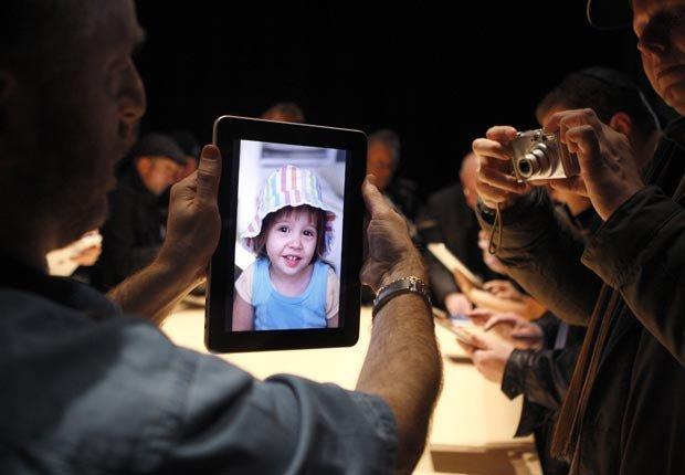 Un hombre prueba la exhibición de fotos sobre un nuevo iPad.