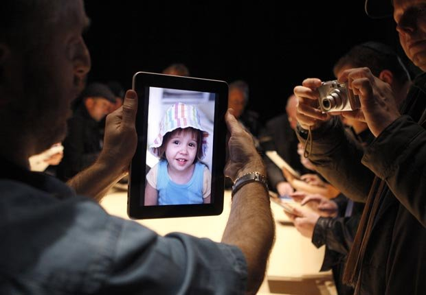 A guest tries out the photo display on a new iPad.
