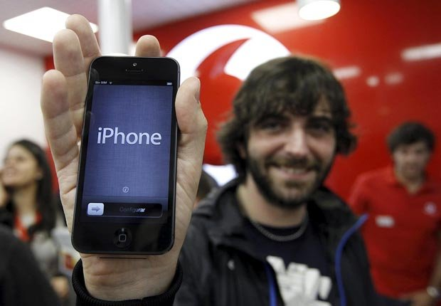 A person holds the Apple iPhone 5 mobile.