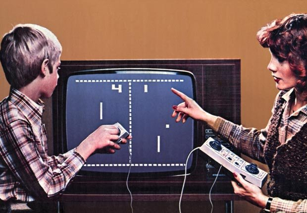 A mother and son play Pong, the first video game that was released in the 1970's.