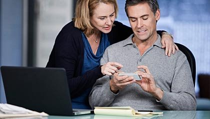 Couple operates cell phone with laptop on desk, Samsung article Innovation50+