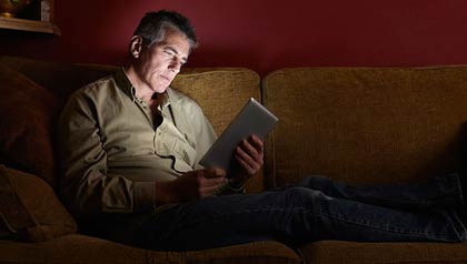 Hombre mirando una serie de televisión en su tableta digital.