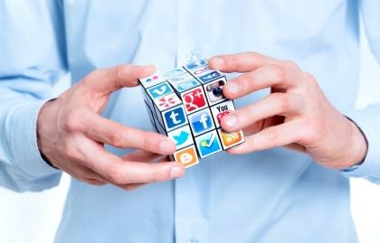 Man resolviendo un cubo de Rubik con los logotipos de medios sociales. Hacer el mejor uso de Facebook, Twitter, Pinterest y Instagram
