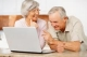 Pareja de adultos mayores usando un computador