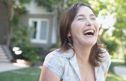 Mujer de pie al aire libre riendo, Espiritualidad: 5 claves para ayudarle a dejar de lado la negatividad
