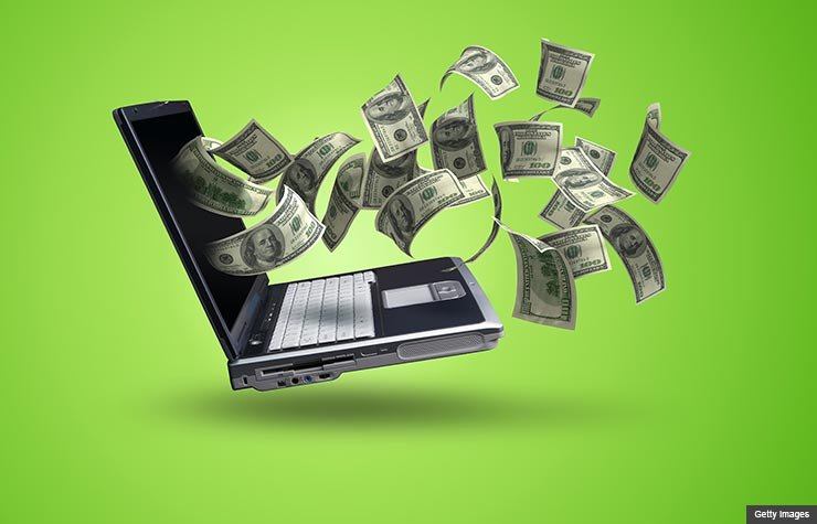 Money flying out from a computer screen, How to Make Money with Old Gadgets and Electronic (Getty Images)
