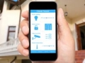 Hombre que sostiene un teléfono inteligente y en el fondo una casa, ¿Qué está de moda en los hogares para conectarse en línea?
