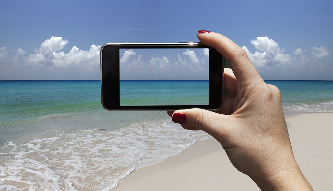 Women Holds Up Phone To Beach To Take A Photo, AARP Home And Family, Personal Technology, Best Phone Editing Tricks For Smartphone