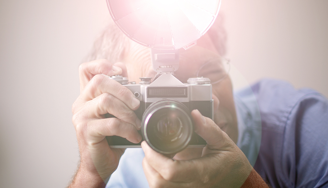 Man Looks Through Camera Viewfinder With Flash Mounted, AARP Home And Family, Personal Technology, 13 Items That Have Been Replaced By The Smartphone