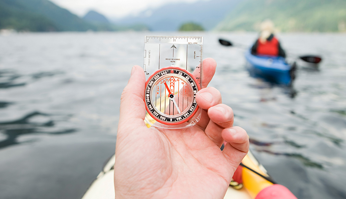 Person In Kayak On Lake Holds Compass, Mountains, AARP Home And Family, Personal Technology, 13 Items That Have Been Replaced By Smartphone