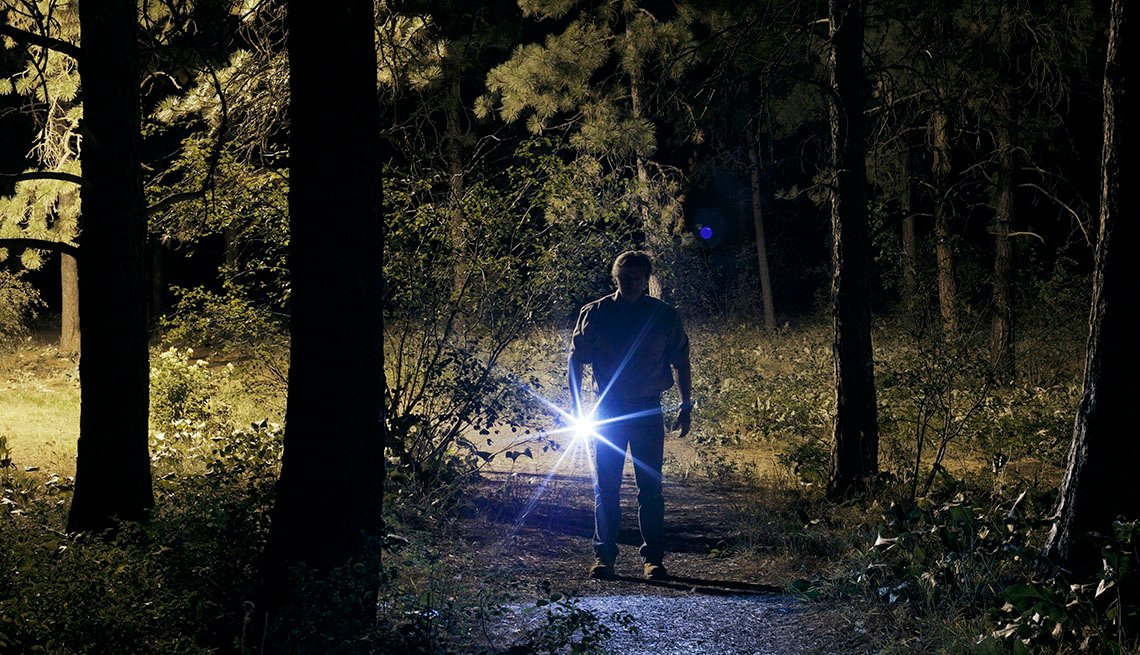 Man Holds Flashlight In Forrest At Night, AARP Holme And Family, Personal Technology, 13 Items That Have Been Replaced By The Smartphone
