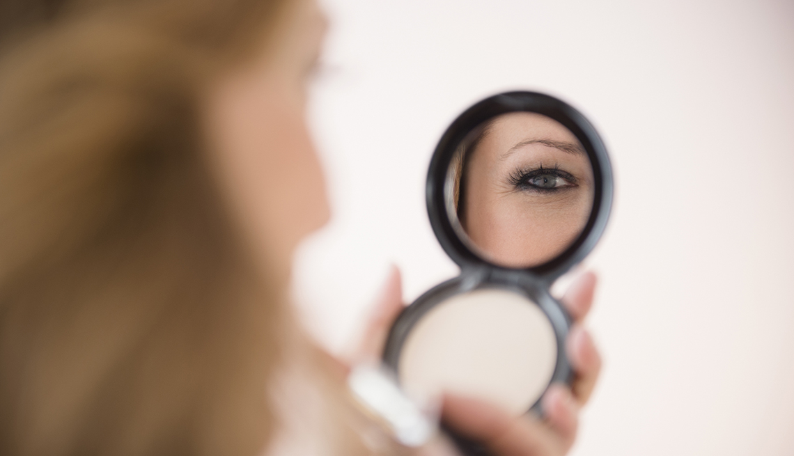 Woman Looks In Her Compact Mirror To Check Her Makeup, AARP Home And Family, Personal Technology, 13 Items That Have Been Replaced By The Smartphone