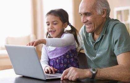 Abuelo con su nieta frente al computador - Cómo ayudar a tus nietos a tener una buena experiencia con la tecnología