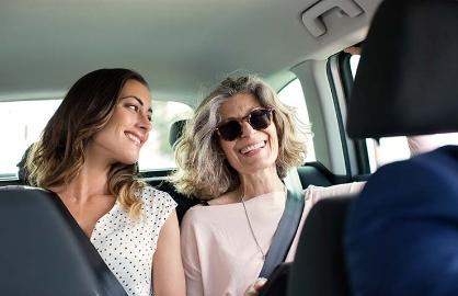 Dos mujeres hablan mientras van en un auto - Cómo te benefician los servicios de auto compartido