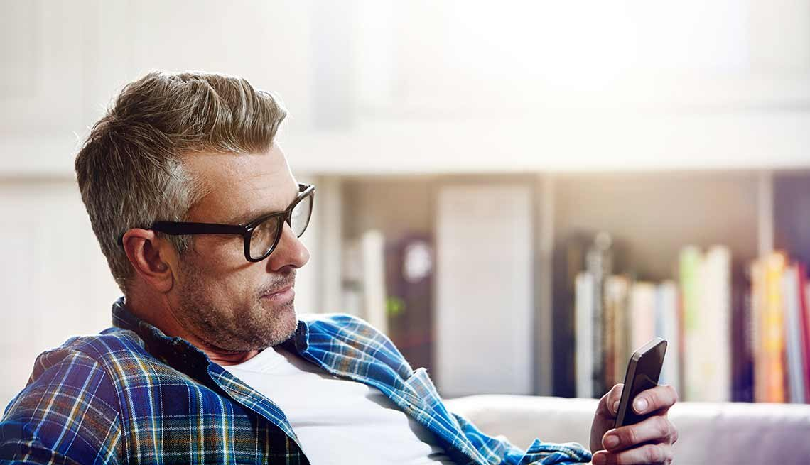 Cómo reducir el estrés con ayuda de apps - Hombre viendo pantalla de teléfono inteligente