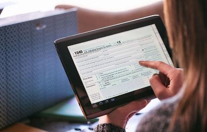 Mujer diligencia sus impuestos en una tableta digital
