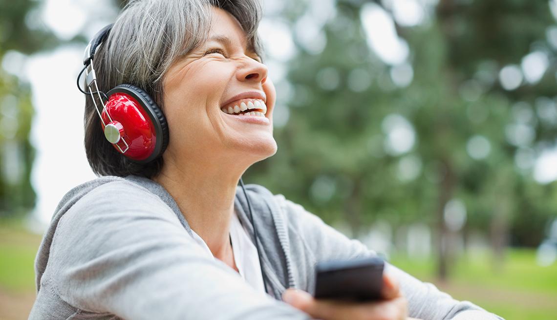 Están hechos para ti los podcasts - Mujer con audífonos puestos sonríe