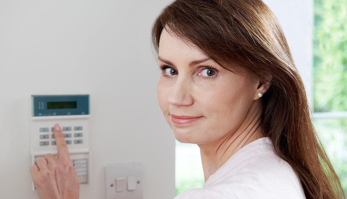 Mujer activando alarma en la casa