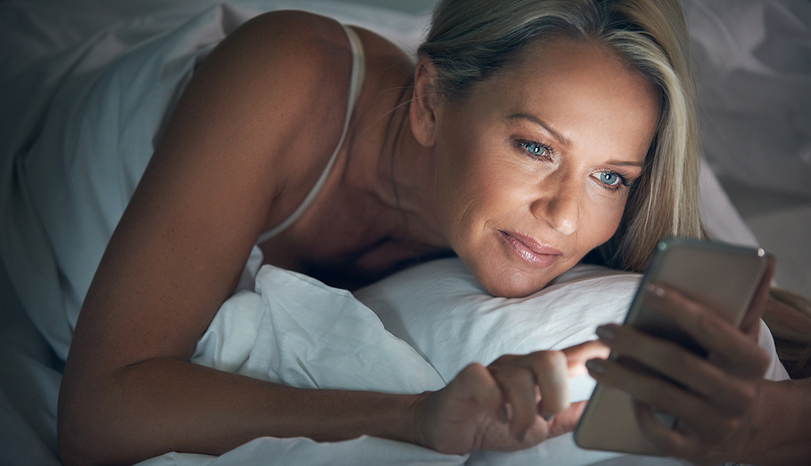 A woman looks at her phone in bed