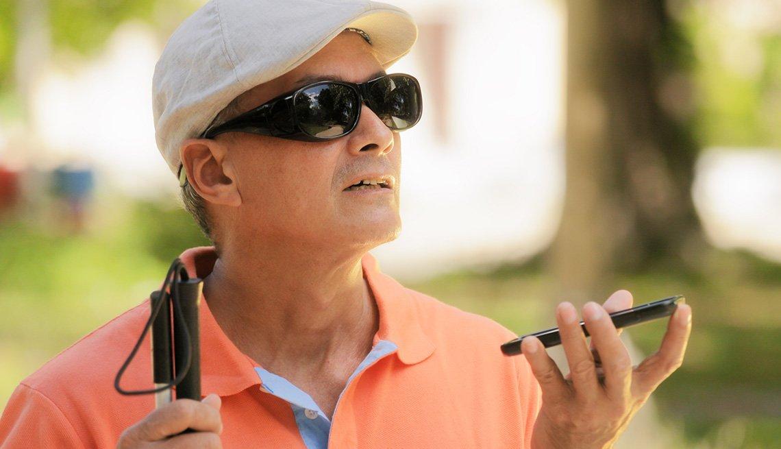 Hombre con discapacidad visual utilizando las funciones de asistente digital y facilidad de acceso en el teléfono móvil.