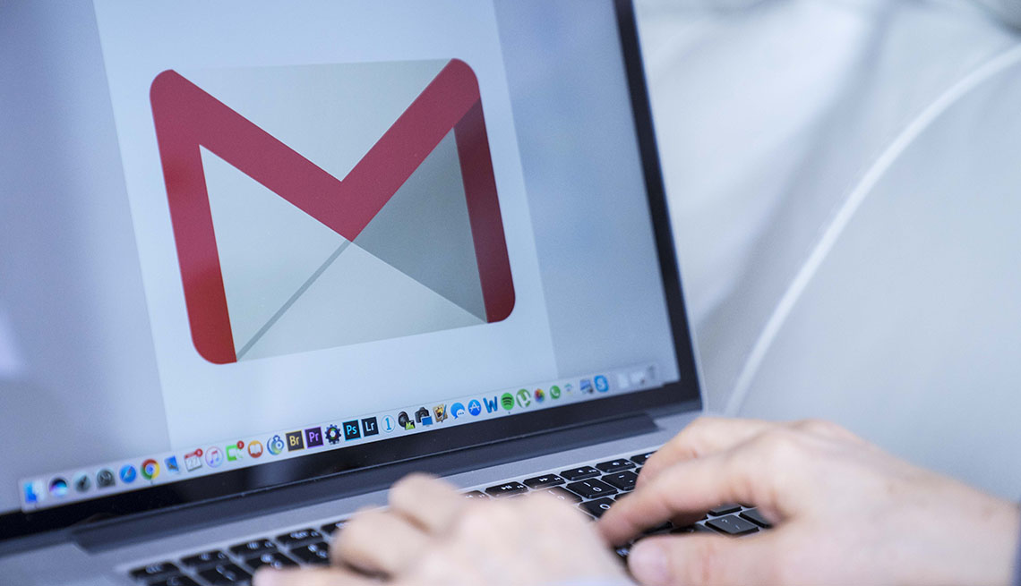 person typing at computer with gmail logo onscreen