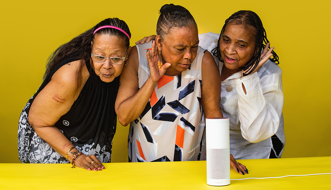 Three women listening to a smart speaker.
