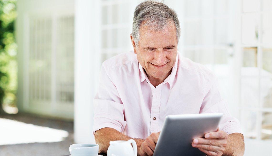 Un hombre mayor sonriente trabaja en una tableta digital.