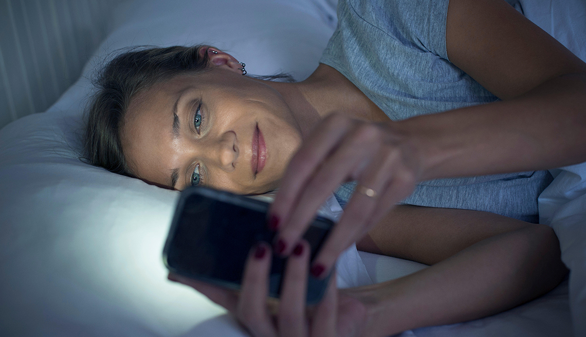 Woman in bed using smartphone