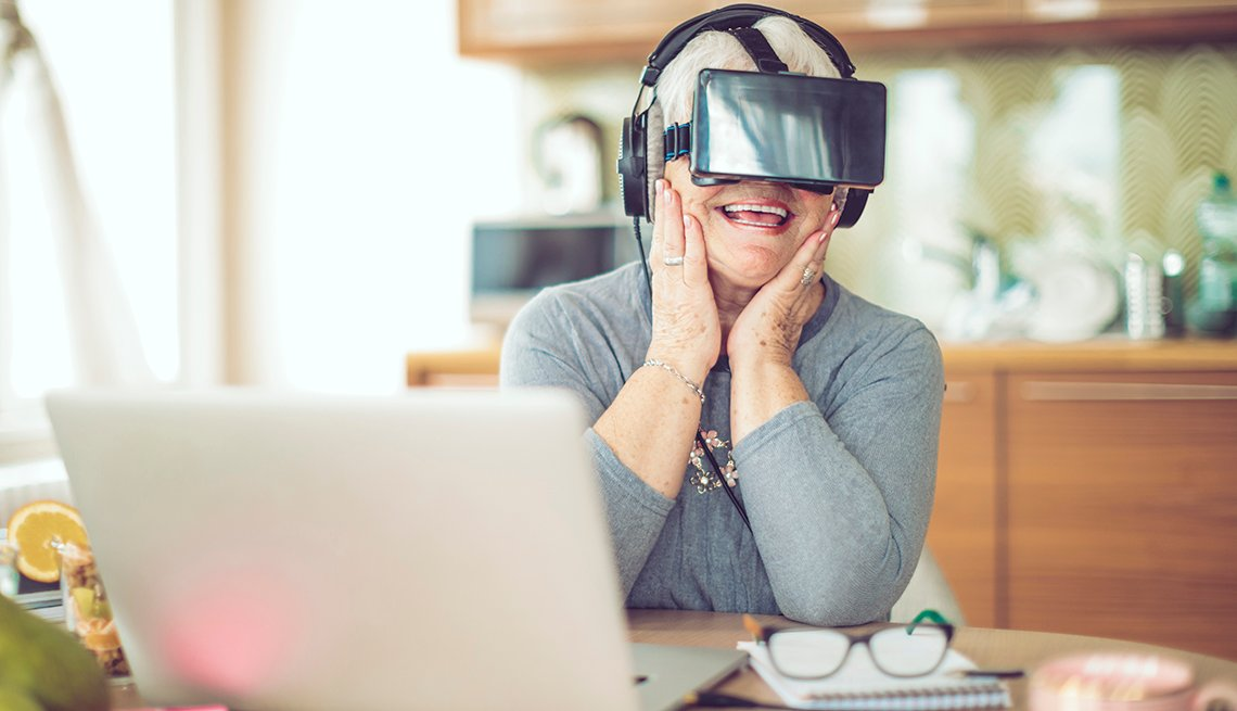 A woman wearing VR goggles at her kitchen table
