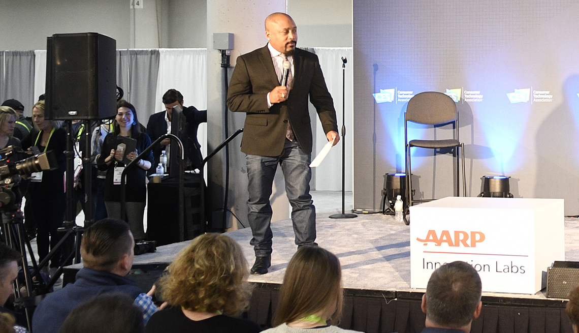 Daymond John on stage, banner reads AARP Innovation Labs