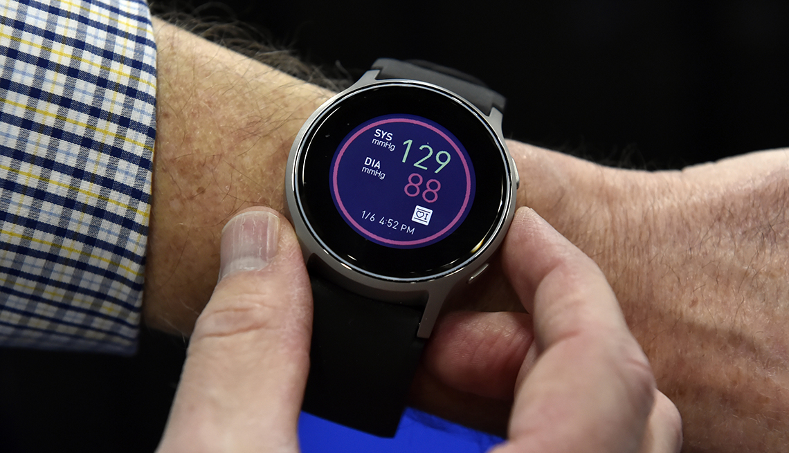 A man pressing buttons on his smartwatch