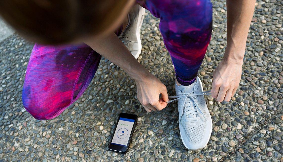 Persona haciendo deporte amarra los cordones de sus zapatos