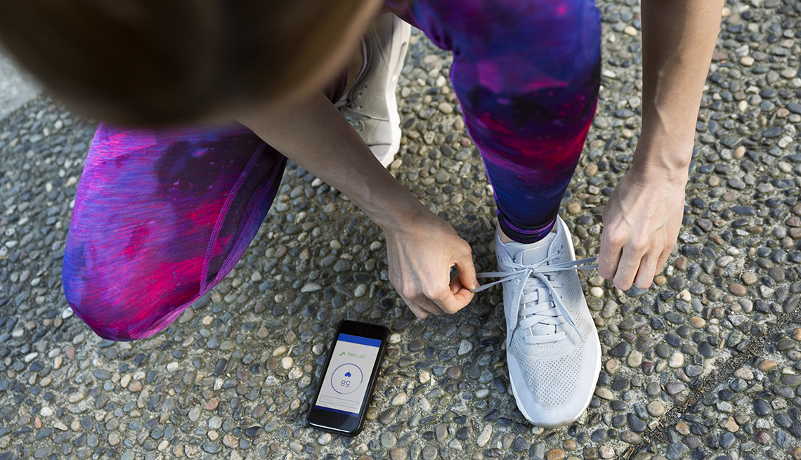 person tying shoes with smartphone on ground