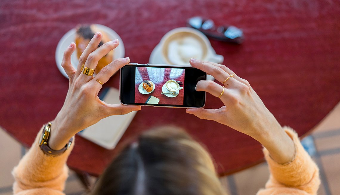 a woman takes a picture on a smartphone of a plate of food and coffee